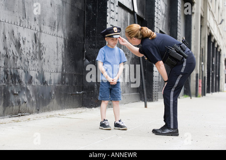 Woman police officer talking to a boy. - Stock Photo