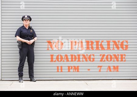 Woman police officer standing in front of a shutter. - Stock Photo