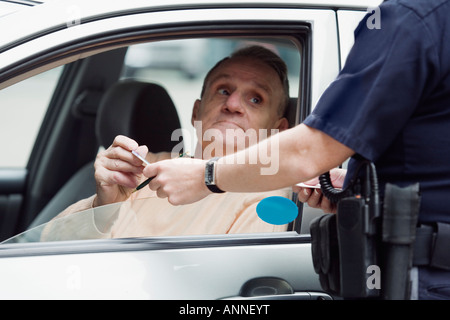 Police sergeant checking driver's license. - Stock Photo