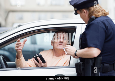 Woman police officer checking driver's license. - Stock Photo