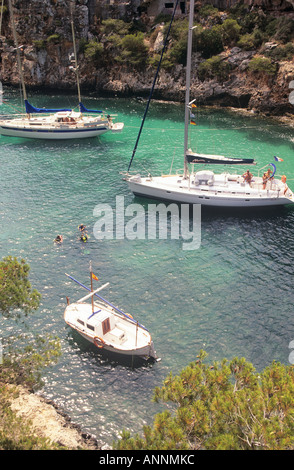A view of yachts anchored in the narrow cove between the pine studded cliffs at the resort of Cala Pi - Stock Photo