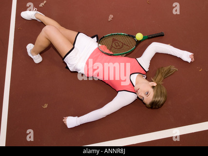 Stock photo showing caucasian teen girl from 15 to 17 years lying down on tennis court She is either resting or - Stock Photo