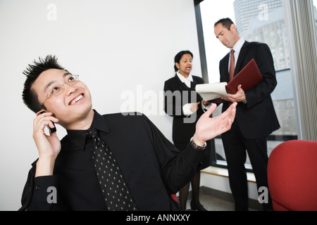 View of architect talking on moblie phone with businesswoman and man discussing. - Stock Photo