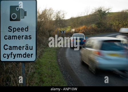 Horizontal view of traffic speeding along a country road by a speed camera warning sign - Stock Photo