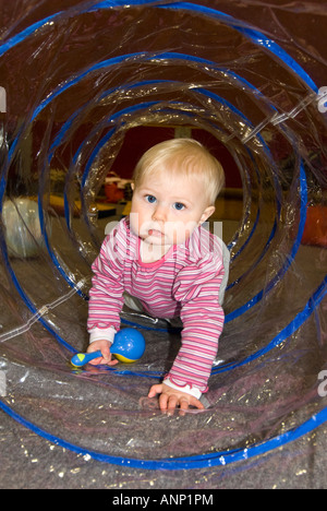 Vertical close up of a pretty Caucasian baby girl crawling through a see through plastic tube at a toddler group - Stock Photo