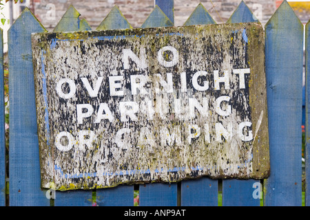 Scruffy old sign advertising no overnight parking or camping - Stock Photo