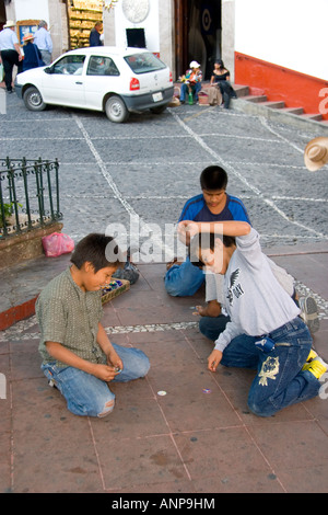 Mexican boys playing a game of pogs in the plaza at Taxco in the State of Guerrero Mexico - Stock Photo
