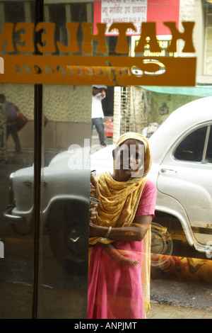 A woman begs from outside of a confectioners, near to Sudder Street, Kolkata, India. She is not permitted to enter - Stock Photo