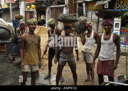 Workers pose for a photograph on a construction site near the Kali Ghat in Kolkata, India. - Stock Photo