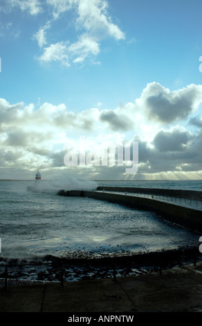 Waves crashing over end of harbour, Castletown - Stock Photo