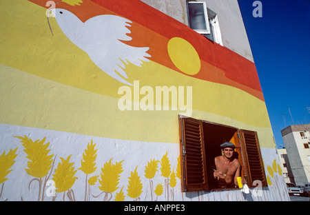 Bird of peace mural and resident artist at his open window Las Palmas town Vegueta Gran Canaria Canary Islands Spain - Stock Photo
