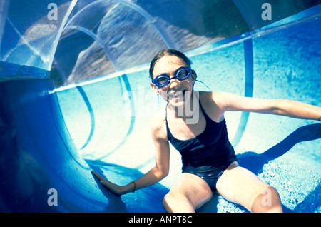 Girl on a water slide at an aqua park - Stock Photo