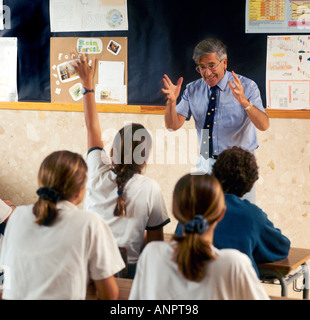 Hand up classroom male Teacher excited and enthused by teenage girl pupil's hands up answer response in senior school - Stock Photo