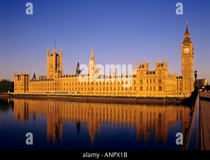 Houses of Parliament illuminated by sunrise reflected in the still River Thames at high tide from Westminster Bridge - Stock Photo