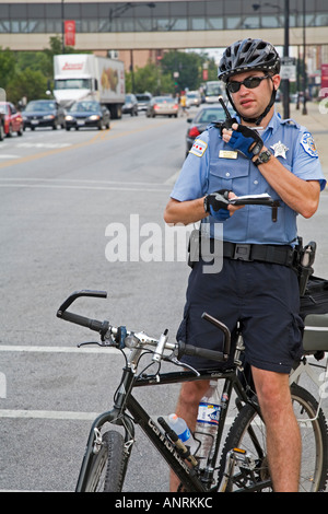 Chicago Illinois A bicycle policeman in Chicago talks on his radio - Stock Photo
