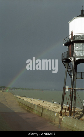 rainbow in dark sky after storm with lighthouse on sea shore - Stock Photo