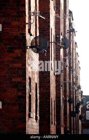 Myriad of satellite dishes and surveillance cameras fixed to side of tenement block in Barrow-in-Furness, Cumbria, - Stock Photo