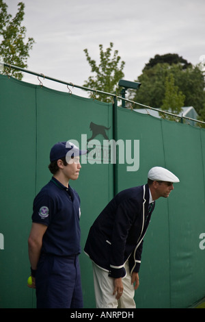 A ball boy and linesman await the next move in the match on an outside court during the Wimbledon Lawn Tennis Championships. - Stock Photo
