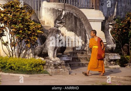 An orange clad monk walking between the 16th century sanctuaries in the compound of Wat Prathat on Doi Suthep mountain - Stock Photo