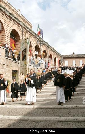 Procession of priests leading into Amandola Church during the  'Processione delle Canestrelle' - Stock Photo