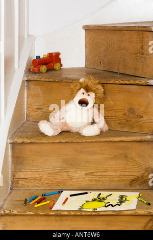 Child's drawing, cuddly toy and wooden train on stairs - Stock Photo