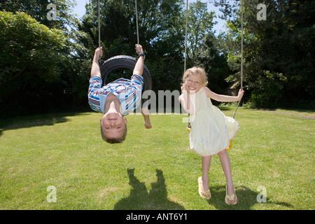 Boy and girl on swings - Stock Photo
