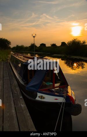 Narrowboat moored at on a pontoon at sunset - Stock Photo