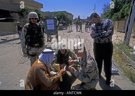 US security forces helping an Iraqi man in Kirkuk Iraq. - Stock Photo