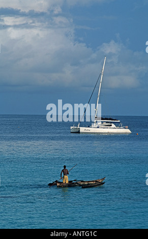 Fisherman sets out in his dug out outrigger canoe Modern yacht beyond Nungwi Northern tip of Zanzibar Tanzania East - Stock Photo