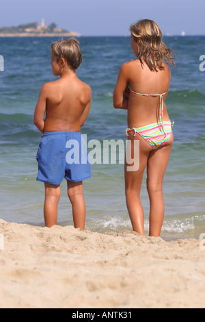Young boy and girl together on holiday beach watching the sea - Stock Photo