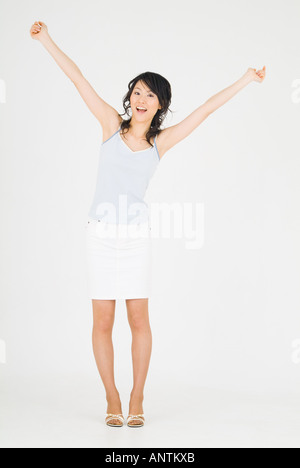 Young woman standing with arms outstretched - Stock Photo