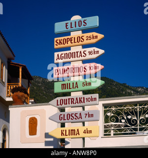 Colourful signpost with destinations and distances in kilometres pointing both ways on Skopelos Island Northern - Stock Photo
