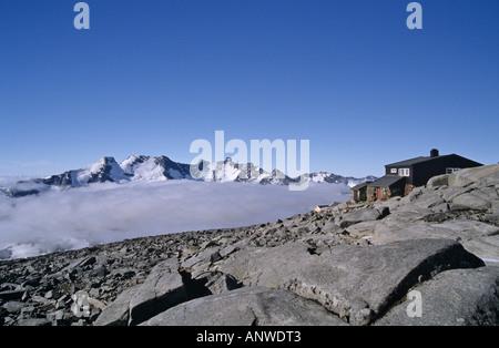 Mountain hut on the Fannaråken, and behind the Hurrungane peaks, Jotunheimen, Norway - Stock Photo