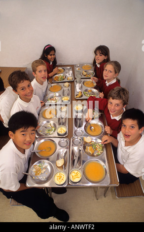 MULTICULTURAL HEALTHY SCHOOL MEALS DINNERS Group of multi ethnic junior school students having healthy balanced - Stock Photo