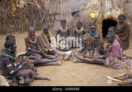 A group of women and children wit in a circle, discussing recent events, in a Bume tribal village, in Ethiopia's - Stock Photo