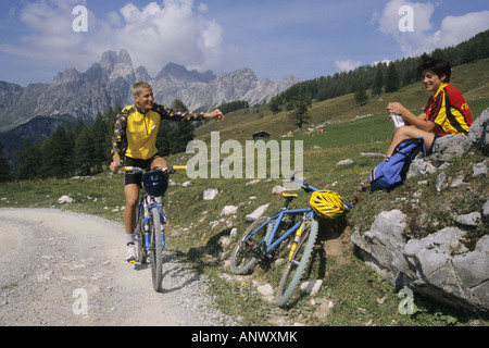 couple with mountainbikes having a break in the Alps, Alps - Stock Photo