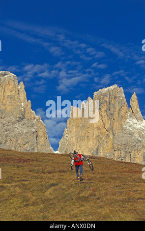 mountainbiker on his way up with the bike over his shoulder, Italy, Suedtirol, Dolomites - Stock Photo