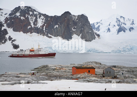 An Antarctic cruise ship sits at anchor behind a a Gentoo penguin colony on Petermann Island - Stock Photo