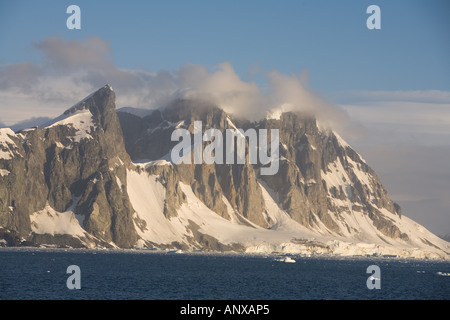 Unnamed peaks on the west coast of the Antarctic Peninsula in Grabam Land tower over the harsh Antarctic Coast - Stock Photo