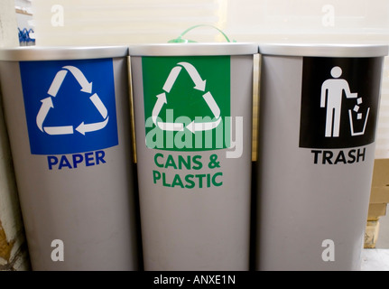 Paper recycling and cans and plastic recycling and trash bins in a warehouse - Stock Photo