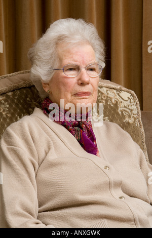An elderly lady sitting in an armchair - Stock Photo