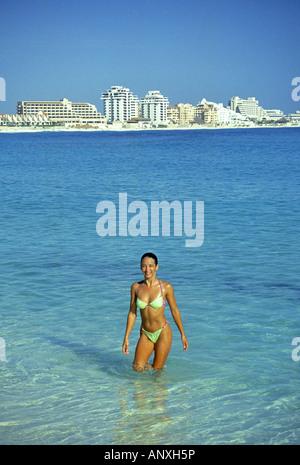 A young pretty Mexican girl in a bikini enjoys a beach and warm caribbean water, Cancun Mexico. - Stock Photo