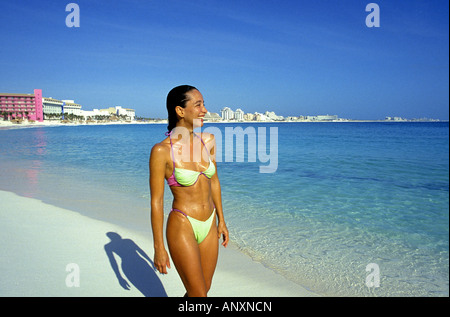 A pretty young Mexican girl in a bikini enjoys beautiful beach in the hotel district of Cancun Island, Mexico. - Stock Photo
