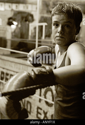A strong moody black and white portrait of a young boxer wearing his boxing gloves and standing in the corner of - Stock Photo