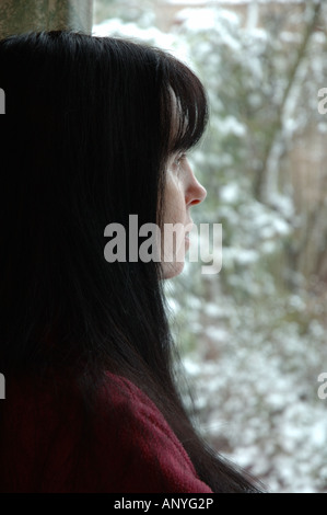 UK, England, woman gazing out of window in winter - Stock Photo