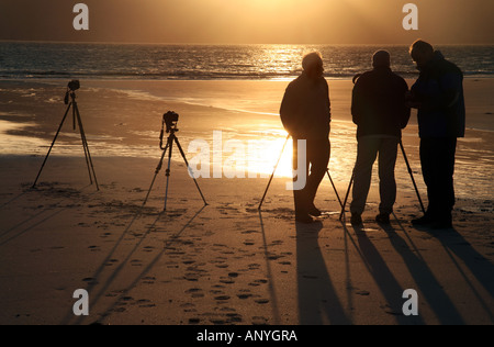 A group of photographers silhouetted against the sunset, Laig Bay, Isle of Eigg, Western Isles, Scotland, UK - Stock Photo