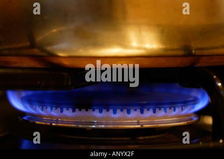 Saucepan cooking over gas flame on cooker hob England United Kingdom - Stock Photo