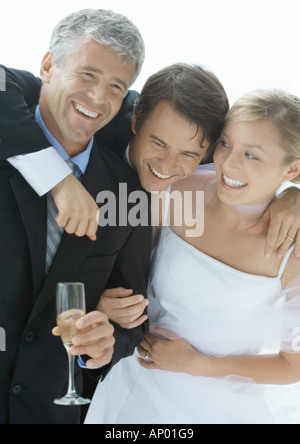 Bride and groom with father, laughing - Stock Photo