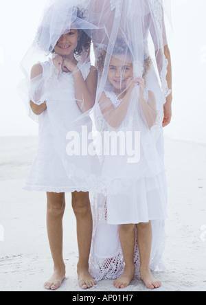 Flower girls standing underneath bride's veil on beach - Stock Photo