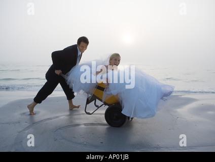 Groom pushing bride in wheelbarrow on beach - Stock Photo